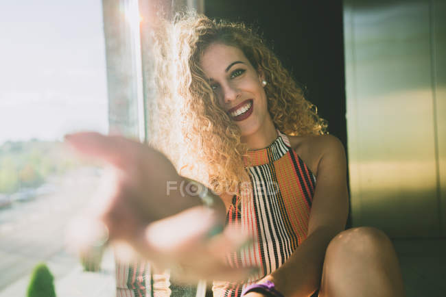 Young curly woman sitting in bright sunshine and outstretching blurred hand with smile — Stock Photo