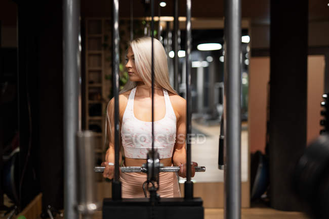Blond athletic woman in sportswear doing exercise in gym — Stock Photo