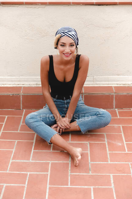Smiling barefoot woman in striped headscarf sitting on tile floor near wall and looking at camera — Stock Photo
