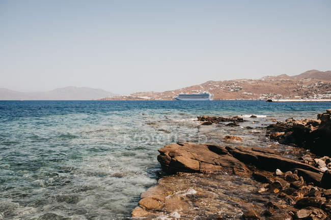 Picturesque view of rocky coast near azure waving sea in Mykonos, Greece — Stock Photo