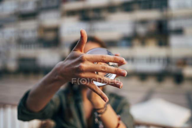 Крупным планом женские руки, держась размытый фон хрустальный шар перед лицом — стоковое фото