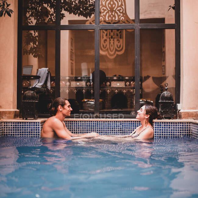 Vista lateral del joven hombre guapo y atractiva mujer de pie en la piscina y cogidas de la mano en el fondo de la puerta de cristal - foto de stock