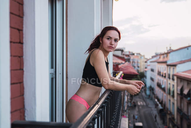 Portrait of young woman with dark hair in lingerie and black crop top standing at balcony on background of city — Stock Photo