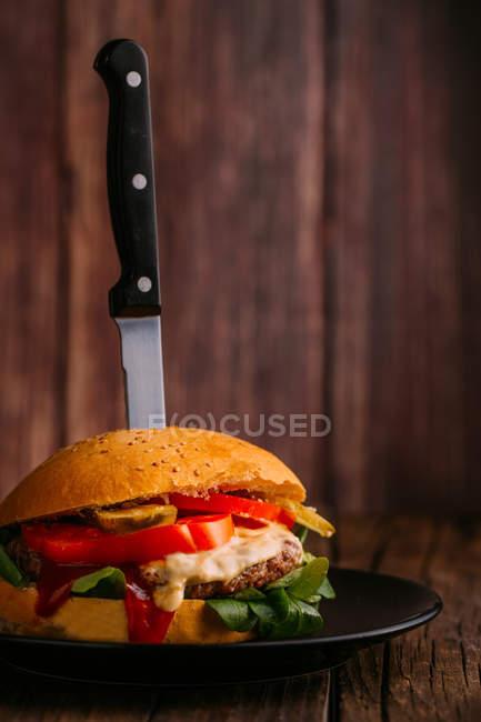 Вкусный гамбургер для гурманов с ножом на тарелке на темном деревянном фоне — стоковое фото