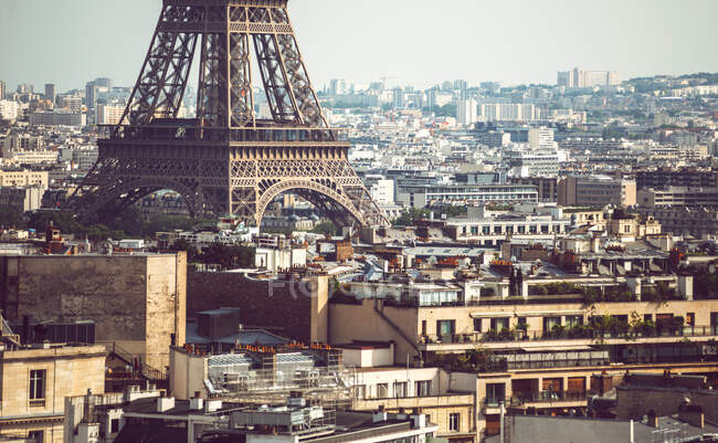 Подвал Эйфелевой башни, стоящий среди зданий на фоне городского пейзажа в Париже — стоковое фото