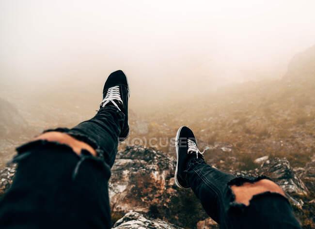 Jambes de touriste méconnaissable assis sur la falaise dans la journée brumeuse. — Photo de stock