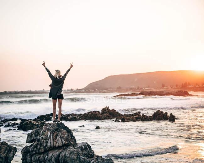 Назад вид женщины-туристки, стоящей с распростертыми руками на прибрежном камне и чувствующей свободу на берегу моря. — стоковое фото
