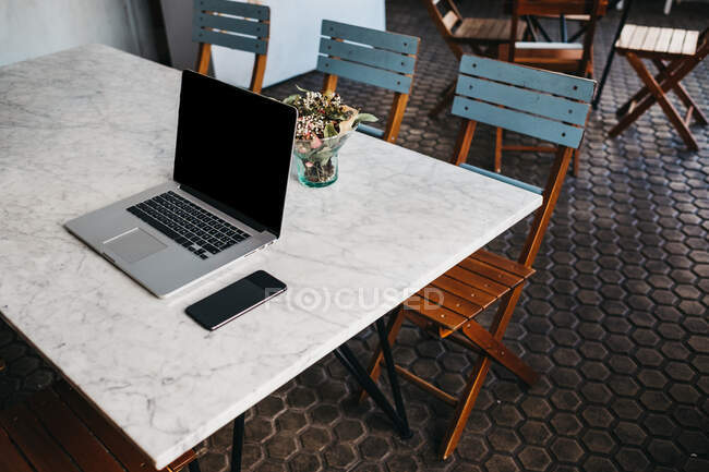 Table with laptop and smartphone on top with small vase of flowers in cafeteria — Stock Photo