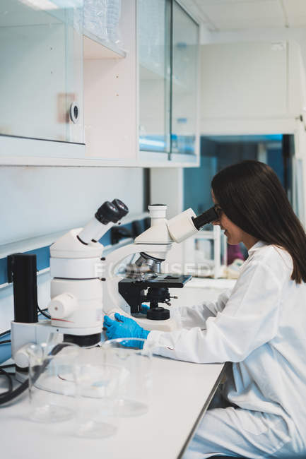 Brunette femme en uniforme en utilisant le microscope en laboratoire — Photo de stock