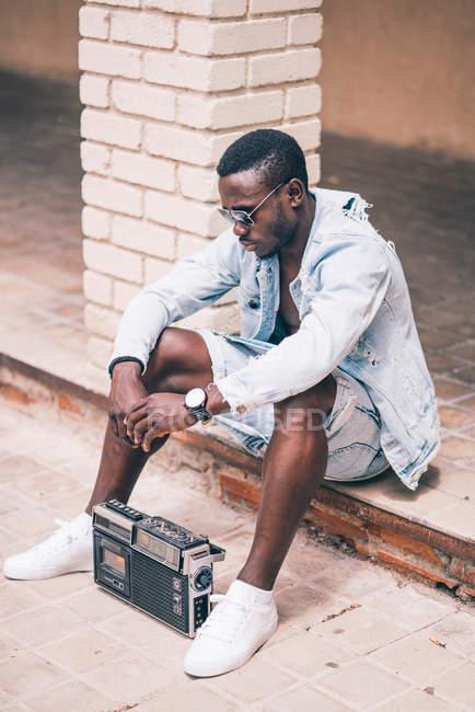 Uomo nero seduto sul pavimento con dispositivo radio vintage — Foto stock