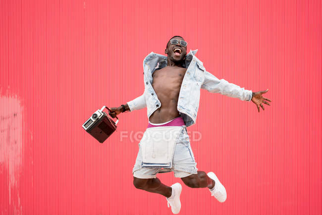 African american man jumping with vintage radio device on red background — Stock Photo