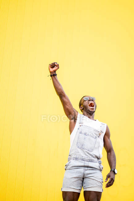 Funky happy man in glory with clenched fist on yellow background — стоковое фото