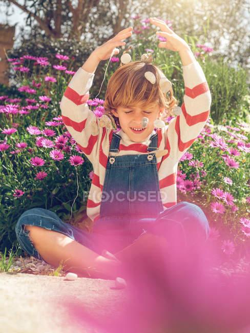 Lindo joven sentado con los ojos cerrados y vomitando guijarro en el jardín - foto de stock