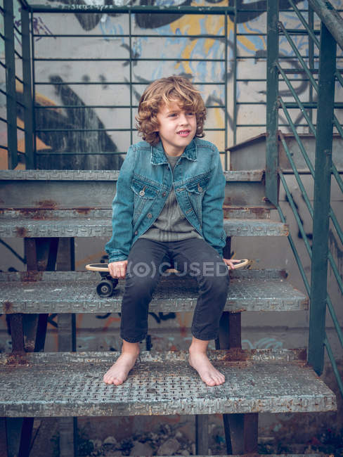 Barefoot boy sitting on stairs with skateboard — Stock Photo