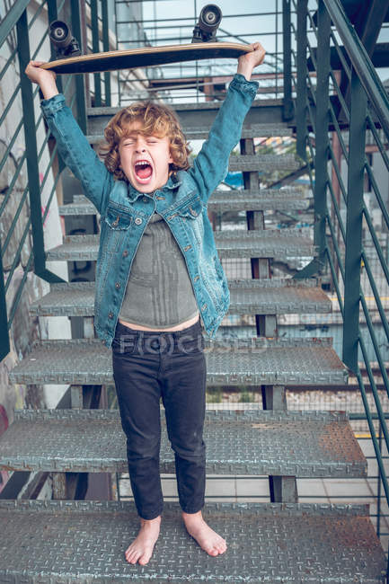 Shouting barefoot boy with skateboard standing on stairs — Stock Photo