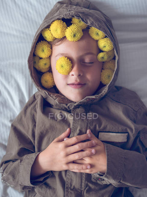 Tranquil cute boy in wreath of yellow flowers lying on bed — Stock Photo