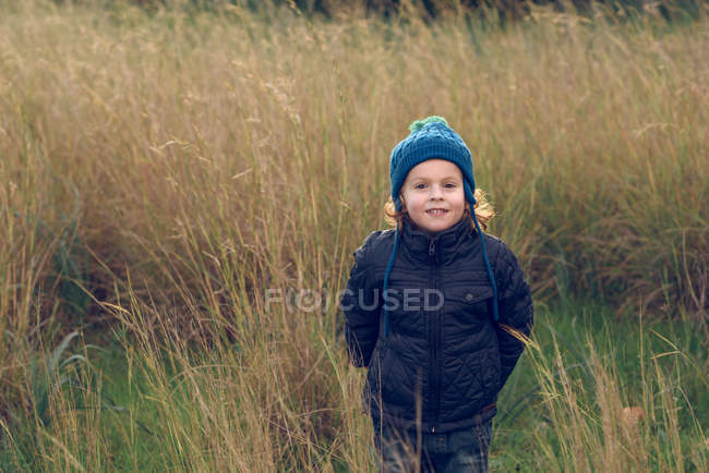 Cheerful little boy standing in grass — Stock Photo