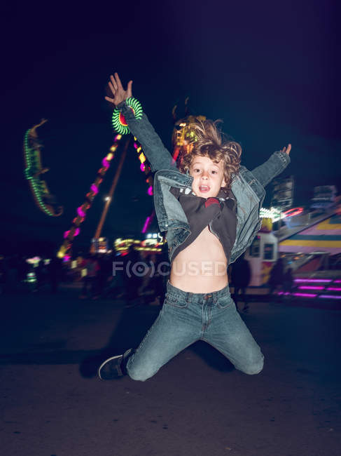 Cheerful little boy looking at camera and jumping on background of carousels on funfair — Stock Photo