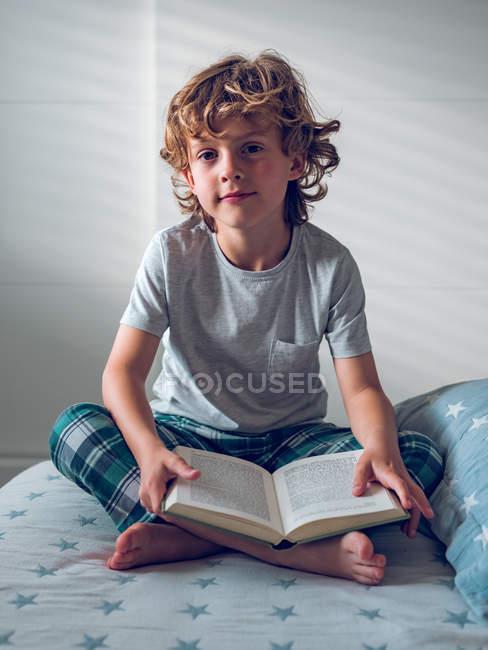 Bonito menino de pijama sentado na cama confortável e lendo bom livro — Fotografia de Stock