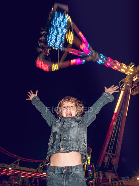 Emotional little boy standing with hands up on the background of carousel at night — Stock Photo