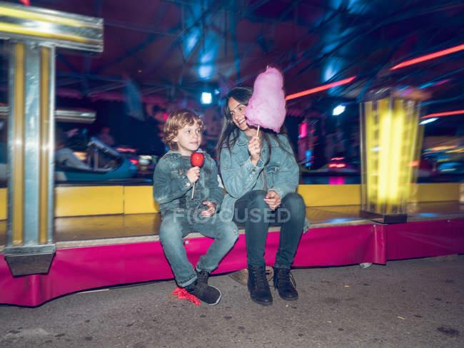 Mulher alegre com fio dental de doces e menino com maçã sentado na feira — Fotografia de Stock