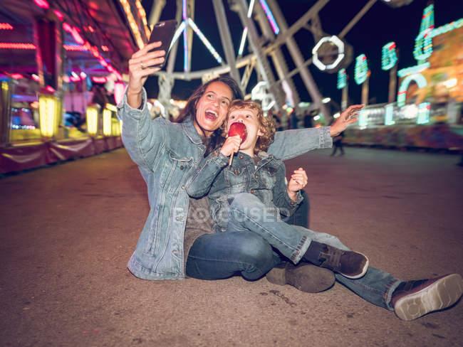 Mãe e filho tomando selfie na feira — Fotografia de Stock