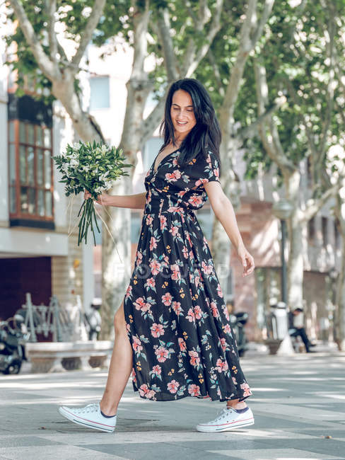 Side view of smiling brunette woman walking with bunch of flowers on the street in sunny day — Stock Photo