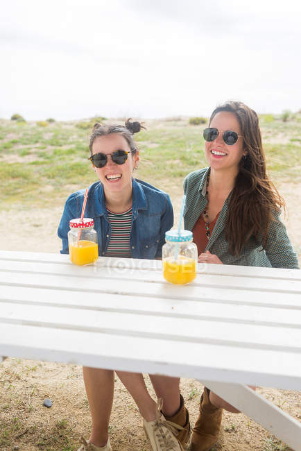 Smiling women having fun with jars with juice — Stock Photo