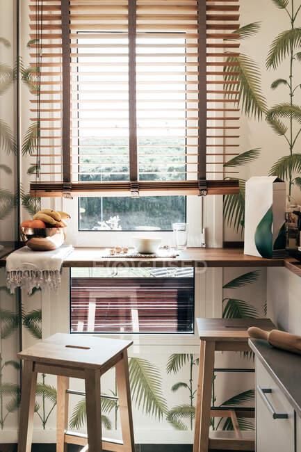 Deux tabourets et étagère étroite près de la fenêtre dans petite cuisine d'appartement élégant — Photo de stock