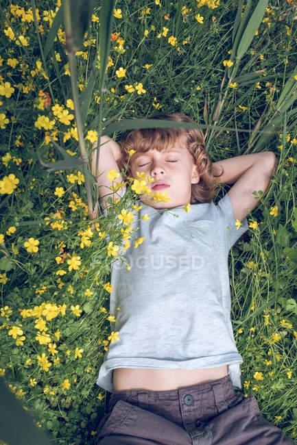 Mignon petit garçon rêvant avec les yeux fermés tout en étant couché sur l'herbe haute avec des fleurs colorées — Photo de stock
