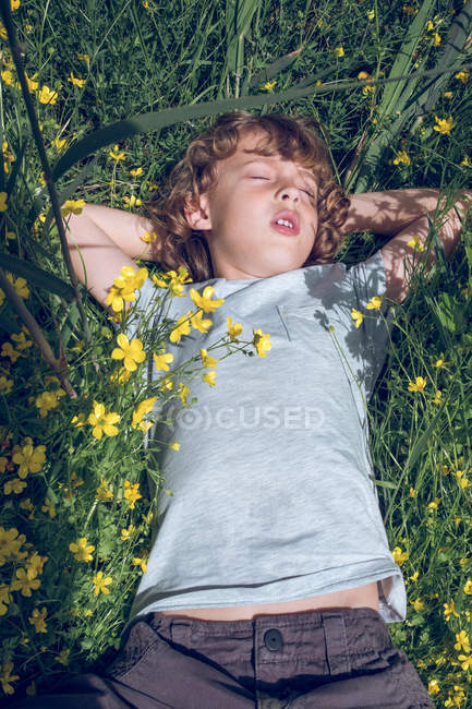 Cute little boy dreaming with closed eyes while lying  on high grass with colorful flowers — Stock Photo