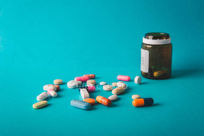 Multicolored pills and capsules with jar on blue background — Stock Photo