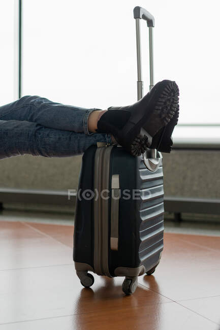 Crop legs of lady in jeans and boots on plastic luggage bag with handle in airport in Porto, Portugal — Stock Photo