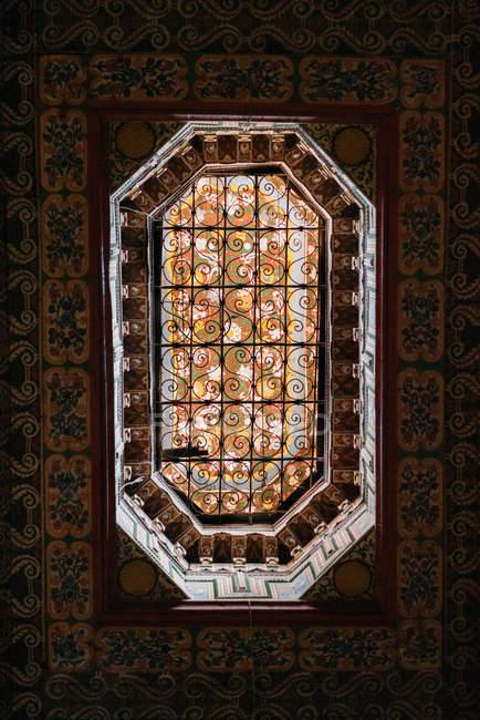 Finestra dell'annata con inferriate di sicurezza in acciaio e parete modellata — Foto stock