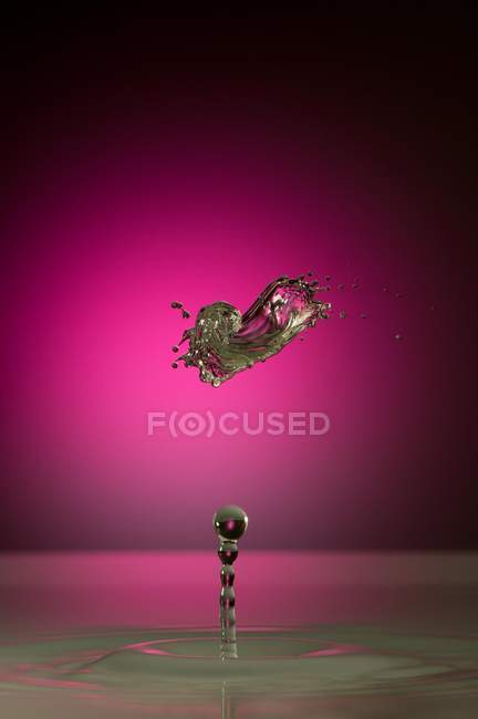 Closeup of splash of transparent liquid of color on pink background — Stock Photo