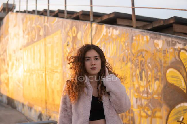 Retrato de mujer joven en traje de moda tocando el pelo rizado y mirando a la cámara mientras está de pie cerca del estadio de pie en el día soleado - foto de stock