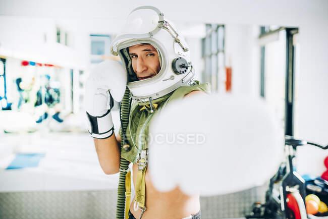 Поза в интерьере спортзала со шлемом астронавта .. — стоковое фото