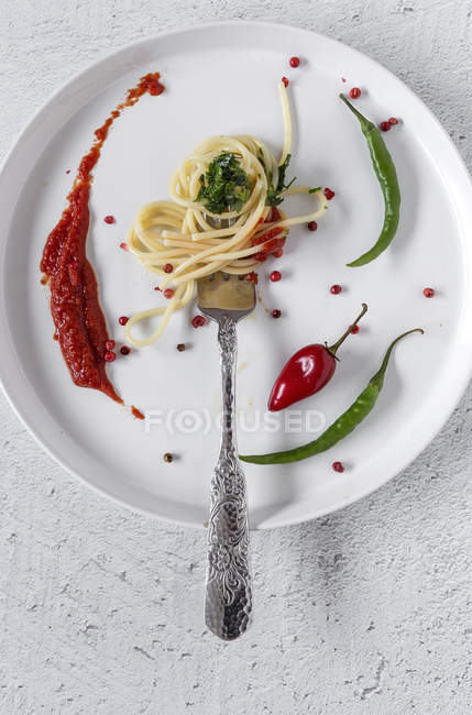 Spaghetti au pesto de tomates et sauce sur fourche sur fond blanc — Photo de stock