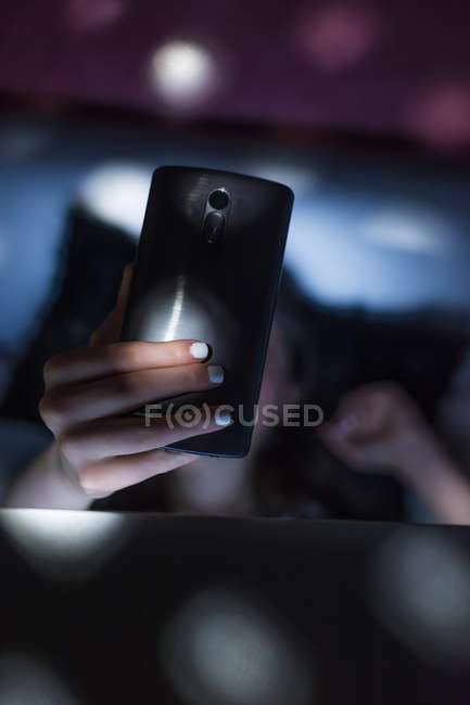Close-up of female hand using smartphone in blurred dark room — Stock Photo
