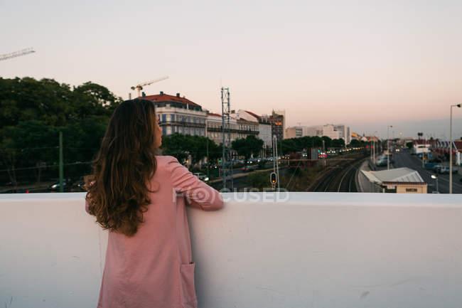 Sogno giovane guardando lontano sulla passerella sopra la strada con le auto — Foto stock