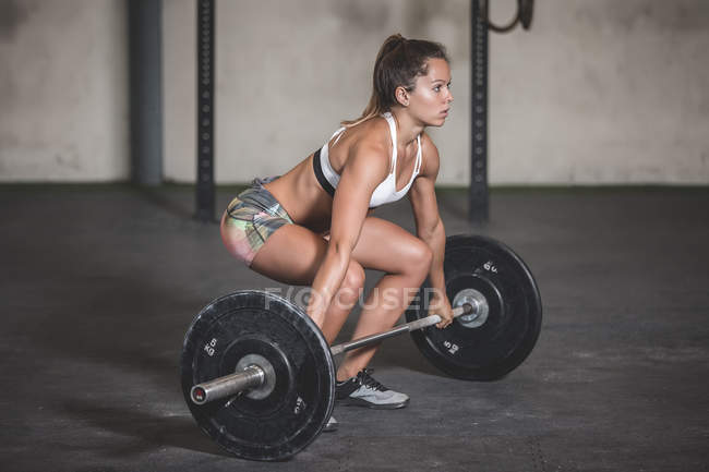 Woman holding barbells with weight plates in sports hall — Stock Photo