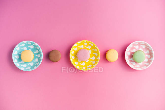 From above bright delicious macarons on plates on pink background — Stock Photo