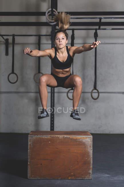 Молода жінка з спортивного одягу стрибає на сходах біля гімнастичних кілець у спортзалі. — стокове фото