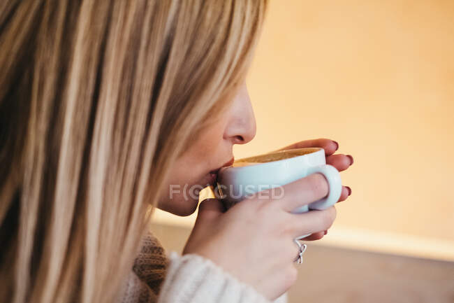 Side view crop attractive woman in sweater holding mug ofhot drink near lips — Stock Photo