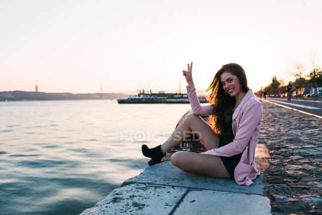 Sorridente giovane donna seduta su argine vicino alla superficie dell'acqua con nave al tramonto e mostrando segno ok — Foto stock