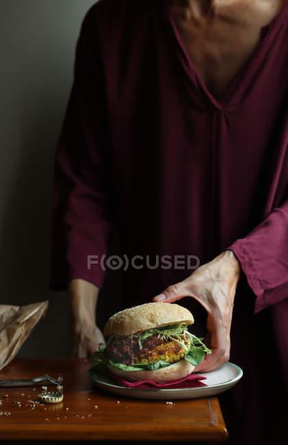 Close-up of woman enjoying veggie burger — Stock Photo