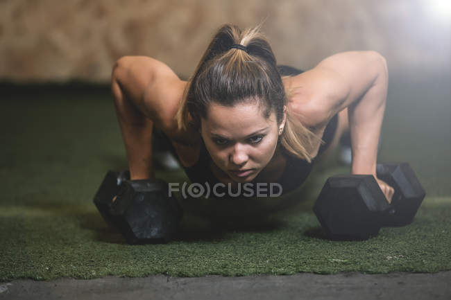 Woman in plank lifting dumbbell in sports hall — Stock Photo