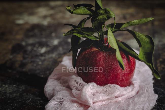 Roher roter Apfel mit Blättern auf dunklem schäbigen Tisch — Stockfoto