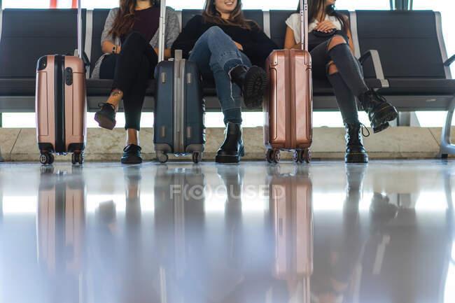 Giovane donna utilizzando smartphone e seduto sul sedile vicino ad altre signore — Foto stock