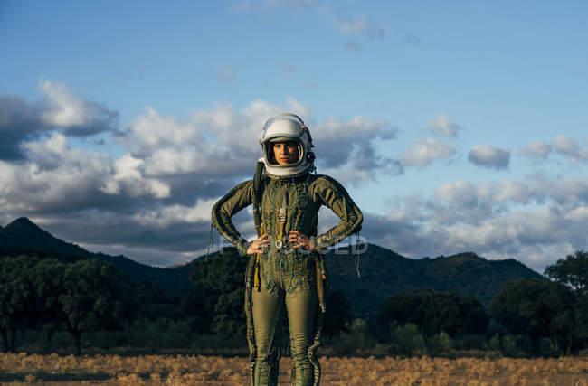 Уверенная женщина-астронавт, стоящая на природе вечером — стоковое фото